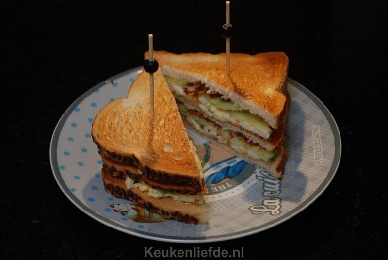 Club sandwich met eiersalade, bacon en komkommer