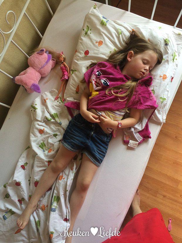 Slapend op bed in haar Mega Mindy badcape en creme op haar neus gesmeerd.